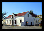 This U-shaped building has a feature peculiar to Hottentots Holland; namely a front gable with small distinctive 'thumb wings' reduced to the width of the edge- mould only. The Police Station, originally a dwelling-house, probably dates from between 1835 Architectural style: Cape Gabled. Type of site: Police Station. Current use: Police station.