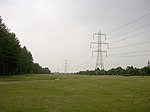 "Power lines between the Dibden Inclosure and the Hythe by-pass, New Forest. Looking NW along the clearing between the Dibden Inclosure (left) and the Hythe by-pass (right). The power lines, which connect Fawley Power Station to the national grid, were there before either the inclosure or the by-pass, so perhaps this gap must have been deliberately left for safety reasons? There are some groups that consider these power lines an intrusion on the beauty of the Forest, representative of the use of the Forest as a soft option for the location of ""unsightly infrastructure"". Still, if you want electricity... are underground cables viable?"