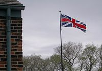 Flag on pole before grey sky and trees in early spring. A modern brick building is visible on the left.