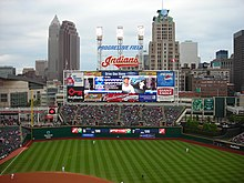 A baseball scoreboard with a skyline in the background