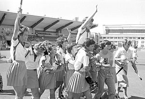 Women in hockey attire celebrate, waving their arms and sticks in the air