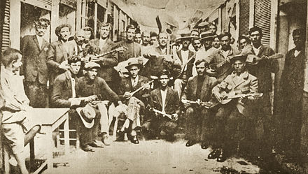 Rebetes in Karaiskaki, Piraeus (1933). Left Markos Vamvakaris with bouzouki. Rembetes Karaiskaki 1933.jpg
