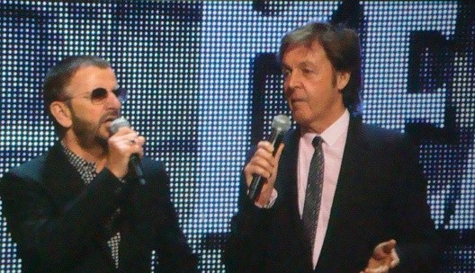 A photograph of two older men, one using a microphone, in front of a large electronic display