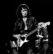 A guitarist, Ritchie Blackmore, is shown playing a Fender electric guitar onstage. He has long hair.