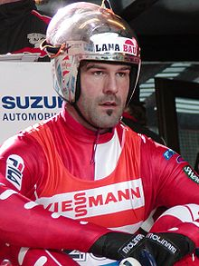 A man with a soul patch wears a red-and-white tight jumpsuit, with a red-and-white vest over it, and a metallic silver helmet with a raised full-faced visor. He is sat on the ground with his arms resting upon his legs.