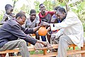 Rwandan old Man playing Igisoro sharing drinks in traditional tool called AGACUMA.jpg