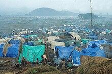 Näkymä pakolaisleirille sumuisena päivänä, jossa on erivärisiä telttoja ja pakolaisia