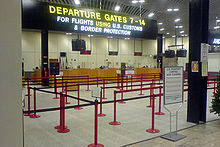 """A row of desks beneath a large sign reading """"For flights using U.S. customs and border protection""""."""