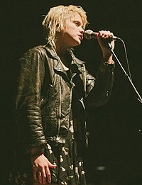 A light-skinned blonde woman wearing a leather jacket is seen singing into her microphone