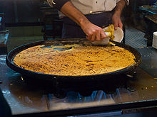 Grande et fine galette cuite de couleur jaune orangée au sortir du four en train d'être servie sur sa plaque.