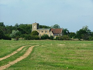 A field with a stone church in the distance, showing an embattled tower on the left, then the nave with a slate roof, and at a lower level the chancel with a red tiled roof