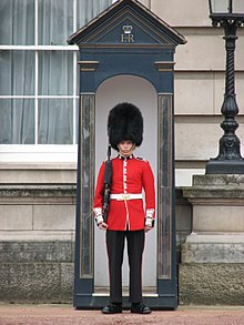 Soldier of the Coldstream Guards, with tunic buttons in pairs, in red tunic and bearskin, guarding Buckingham Palace.