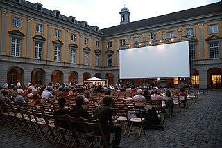 Halb seitlicher blick auf den Arkadenhof der Universität Bonn mit Leinwand und Bestuhlung für das Bonner Sommerkino