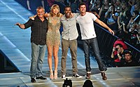 Four people—a middle aged white man in a striped black shirt and jeans, a young white woman in heels and a sparkling dress, a black man in a grey shirt and pants, and a white man in a white tee and jeans, posing together onstage