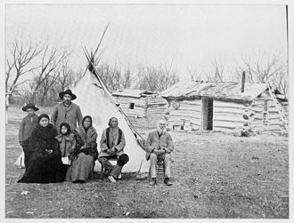Native American identity in the United States - Reservation life has often been a blend of the traditional and the contemporary. In 1877, this Lakota family living at South Dakota's Rose Bud Agency had both tipis and log cabins.