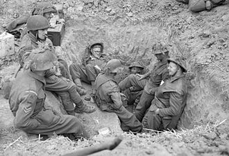 59th (Staffordshire) Infantry Division - Infantrymen of the 1/7th Battalion, Royal Warwickshire Regiment dug in on the outskirts of Caen, France, 9 July 1944.