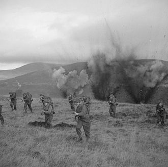 49th (West Riding) Infantry Division - Men of the 11th Battalion, Royal Scots Fusiliers charge with fixed bayonets through 'artillery fire' at a battle school in Scotland, 20 December 1943.