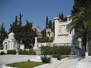 First Cemetery of Athens - Foreground: Tomb of the Pesmazoglou family (right) and Melina Mercouri (middle). Background: Tomb of Heinrich Schliemann (left on the high pedestal).