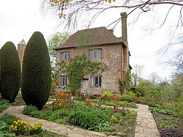 a cottage built of pink brick in the middle of a garden. Spring flowers and two tall Cyprus trees stand in front of the cottage