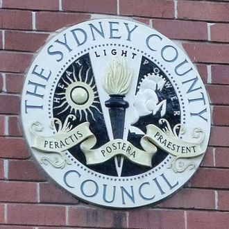 "Sydney County Council - Plaque on exterior wall of The Sydney County Council building with its Latin motto, translated as ""Let the future excel the past""."