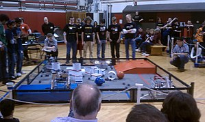 "Bowled Over! - Real world playing field during a typical qualifying round. Similar orientation (i.e. blue is near left) to diagram above. Team 4117 (""Mostly Harmless"", front right in this photo) has scored 10 points by parking in the front parking lot during the autonomous period. Team 5183 (""Sprockets"", back left) has scored 5 points. (Boston University Academy in Boston, Massachusetts on 8 January 2012)"