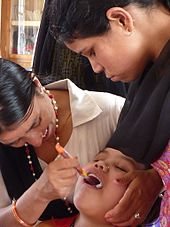 Nepalese women examining patient's mouth in oral health clinic