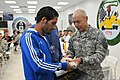 U.S. Army Lt. Gen. Frank G. Helmick, right, deputy commanding general for operations, United States Forces - Iraq, presents paratrooper gifts to members of the Iraqi men, mid-to-long distance Olympic running 111023-A-IK450-036.jpg