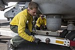 U.S. Navy Aviation Boatswain's Mate (Handling) Airman Alexander Borchick removes a tow bar from the landing gear of a Marine Corps MV-22 Osprey tiltrotor aircraft on the flight deck aboard the amphibious 130807-N-SB587-033.jpg