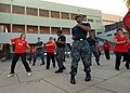 U.S. Sailors assigned to guided missile frigates USS Boone (FFG 28) and USS Thach (FFG 43) take part in Latin-style dancing with a Chilean women's dance group during a community relations project at Escuela Juan 110625-N-ZI300-152.jpg