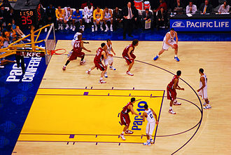 2007–08 UCLA Bruins men's basketball team - UCLA's Kevin Love on the perimeter at Pac-10 Championship game against Stanford at Staples Center, Los Angeles, 2008. Ben Howland and the UCLA bench looks on from the sideline.