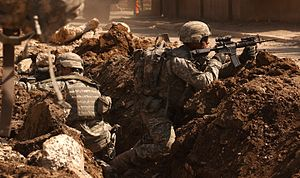 Contemporary history - U.S. soldiers take cover during a firefight with insurgents in the Al Doura section of Baghdad 7 March 2007
