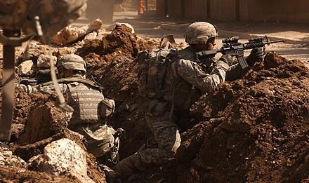 U.S. soldiers take cover during a firefight with insurgents in the Al Doura section of Baghdad 7 March 2007. Army.mil-2007-03-21-084518.jpg