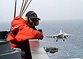 US Navy 030430-N-6410T-510 Seaman Marlin Baggett stands watch as an F-A-18C Hornet from the.jpg