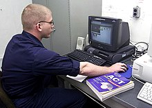 US Navy 030618-N-6920A-002 Personnelman 3rd Class Timothy Gentry logs into a computer terminal set-up for use with the Navy College Program for Afloat College Education (NCPACE) program.jpg