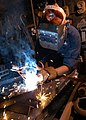 US Navy 040609-N-7748K-005 Hull Maintenance Technician 2nd Class Chris Vilones, of Sacramento, Calif., performs shielded metal arc welding on a bracket to be used on an oxygen tank rack aboard the aircraft carrier USS Enterpris.jpg