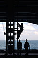 US Navy 041210-N-7405P-010 Fireman Marcus Ross lubricates a sliding payeye kingpost used for cargo transfers during underway replenishments.jpg