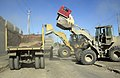 US Navy 041213-N-4614W-019 A U.S. Marine Corps front-end loader joins its Army counterpart in filling contracted Iraqi dump trucks with dirt.jpg