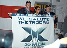 "Hugh Jackman, Halle Berry and Kelsey Grammer hold a flag with the X-Men: The Last Stand logo and the inscription ""We Salute Our Troops"" in a ship's deck."