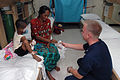 US Navy 060614-N-1577S-003 Navy Aviation Electronics Technician 3rd Class Eric Bloom of Minneapolis, offers cookies to a patient's mother.jpg