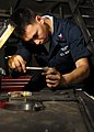 US Navy 080712-N-1281H-105 Aviation Support Equipment Technician 2nd Class Alfonso Navos, from Federal Way, Wash., reinstalls a power steering gear box on a tractor in the hangar bay of the Nimitz-class aircraft carrier USS Abr.jpg
