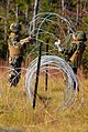 US Navy 081104-N-7367K-009 Gunner's Mate 2nd Class Amanda Hung, left, and Gunner's Mate 2nd Class Ava Dean, both assigned to Naval Mobile Construction Battalion (NMCB) 1, set up concertina wire around the ammunition supply poin.jpg