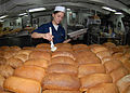 US Navy 090716-N-6720T-017 Culinary Specialist Seaman Samantha Garza butters loaves of fresh baked bread in the bakeshop aboard the aircraft carrier USS George Washington (CVN 73).jpg
