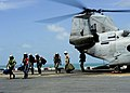 US Navy 101030-N-1531D-176 Patients from Suriname disembark from a CH-46E Sea Knight transport helicopter for medical care aboard the multi-purpose.jpg