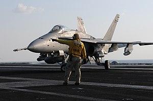 US Navy 120125-N-GZ832-238 Chief Aviation Boatswain's Mate Scott Cook directs an F-A 18C Hornet.jpg