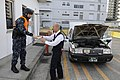 US Navy 120130-N-IO627-028 Hospitalman Derek Sine hands an instruction sheet to a Japanese taxi driver during a vehicle search at a vehicle inspect.jpg