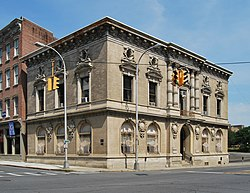 A light tan two-story building with ornamented windows and a colonnade in the center of one side seen from across an intersection, with yellow traffic lights in front.