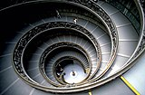 Vast spiral staircase, half in darkness. It is a stepped ramp about 15 meters in diameter, and descends 5 stories at about a 10 degree incline.