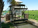 The wrought iron wheel is mounted on the water furrow and shifted by means of reels into the water. Type of site: Bakkiespomp Current use: Agricultural : Water Wheel. This historic water-wheel is one of the few of its kind remaining in South Africa.