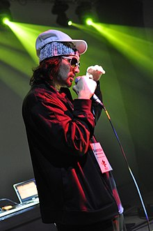 Photograph of a man in a red jacket holding a microphone.