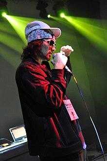 Fotografie eines Mannes in einer roten Jacke, die ein Mikrofon hält.